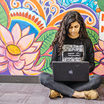 """young woman working on a laptop sitting in front of a colorful mural"""