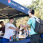 """young man handing a college student a beverage"""