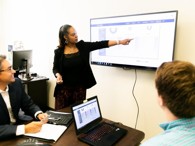 women pointing to a tv monitor displaying data information