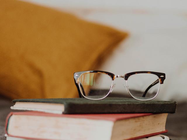 pair of glasses on top of a stack of books
