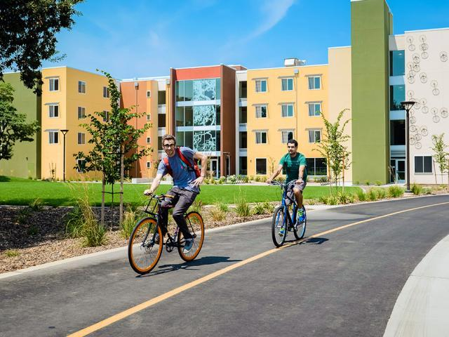 Undergraduate students biking near dorms